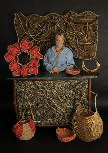 American Master Weaver Tina Puckett of Winsted, CT, pictured with some of her baskets, woven flower sculptures, and a handwoven tiki bar
